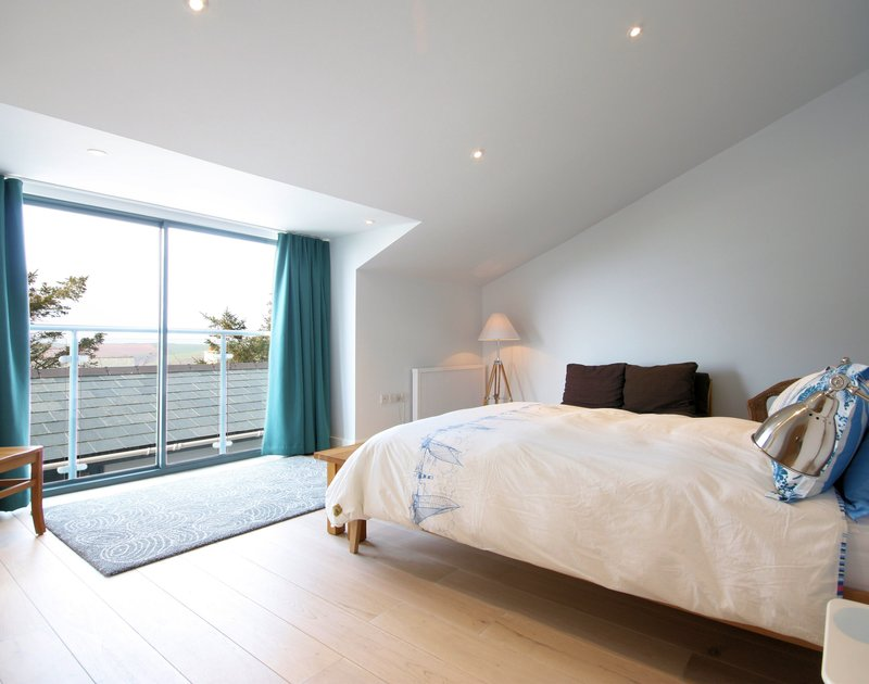 Spacious double bedroom with large sliding windows overlooking the coast at The Crest, a holiday house at Polzeath, Cornwall