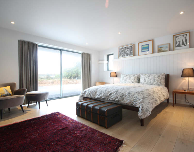 A large double bedroom at The Crest, a superb holiday house at Polzeath, Cornwall, with sliding doors to the garden.