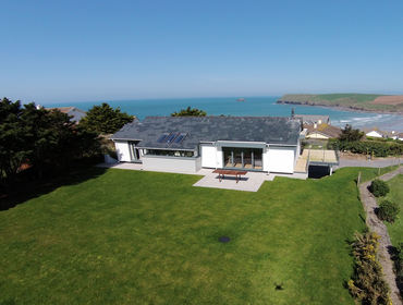 An aerial view of The Crest, a luxury self-catering holiday house with sea and coastal views at Polzeath, Cornwall, with its large garden.