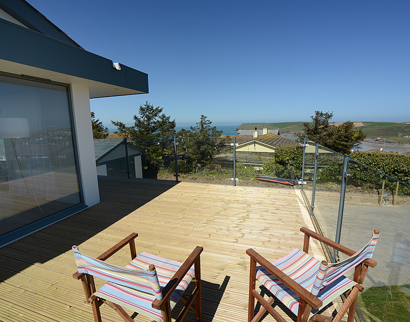 Wooden and glass-walled balcony on the first floor of The Crest, a holiday house in Polzeath, Cornwall, with coastal views.