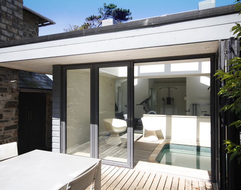 The gym and hot tub at Torquil, an outstanding holiday house at Daymer Bay, Cornwall, with bifold door to the garden