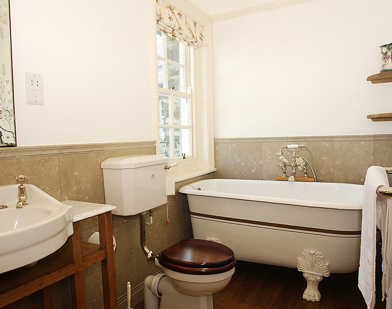 Heritage style bathroom fittings at Torquil, a classic holiday house at Daymer Bay, Cornwall, with claw-foot tub.