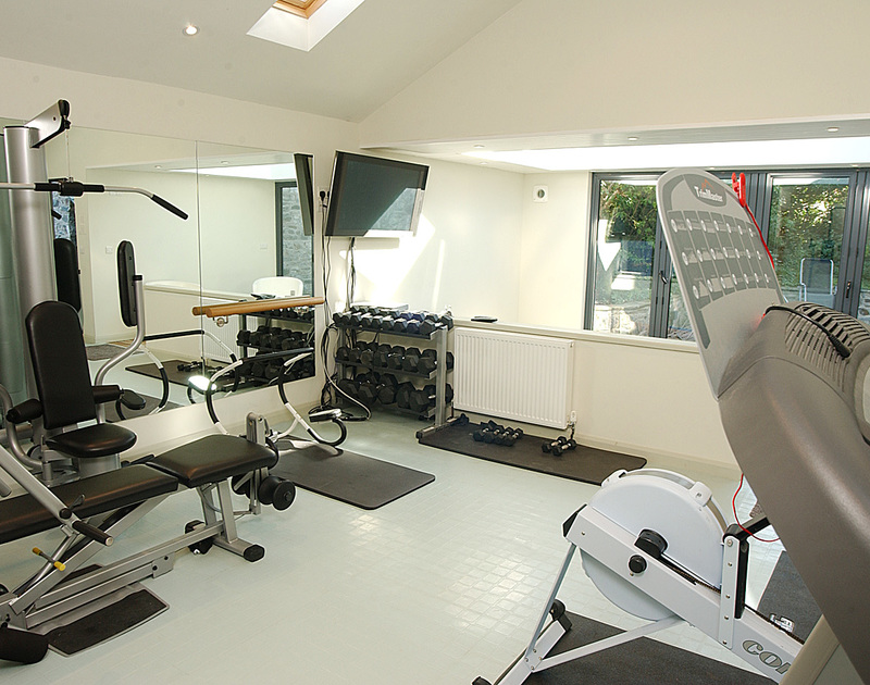 The gym at Torquil, a holiday house at Daymer Bay, Cornwall, with machines and weights.