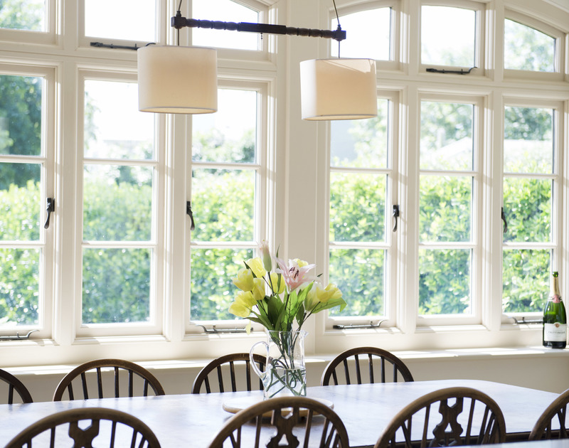 The bright, light dining area of Torquil, a classic holiday house at Daymer Bay, Cornwall, with its long dining room table