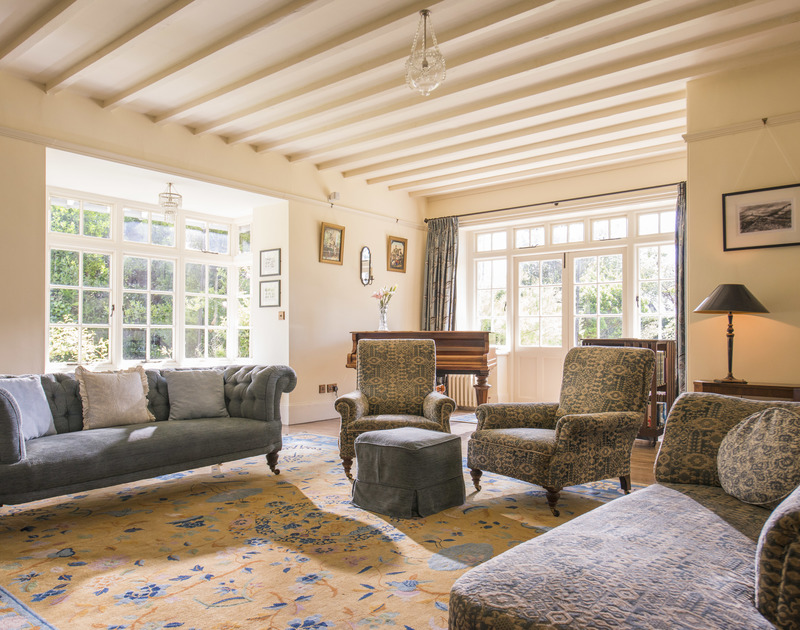The light, spacious and beautifully furnished sitting room of Torquil, a holiday house at Daymer Bay, Cornwall with chesterfield sofa.
