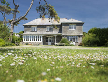 Exterior rear view of Torquil, an attractive stone and slate-hung holiday house at Daymer Bay, Cornwall, with its level lawned garden.