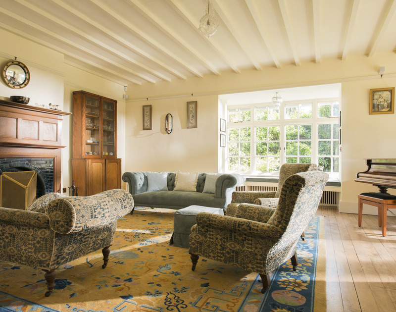 Elegant furniture in the sitting room of Torquil, a coastal holiday house at Daymer Bay, Cornwall, with its large bay window.