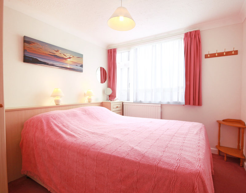 The pink king size bedroom in Sunset, a self catering and dog friendly, family holiday house to rent in Polzeath, North Cornwall.