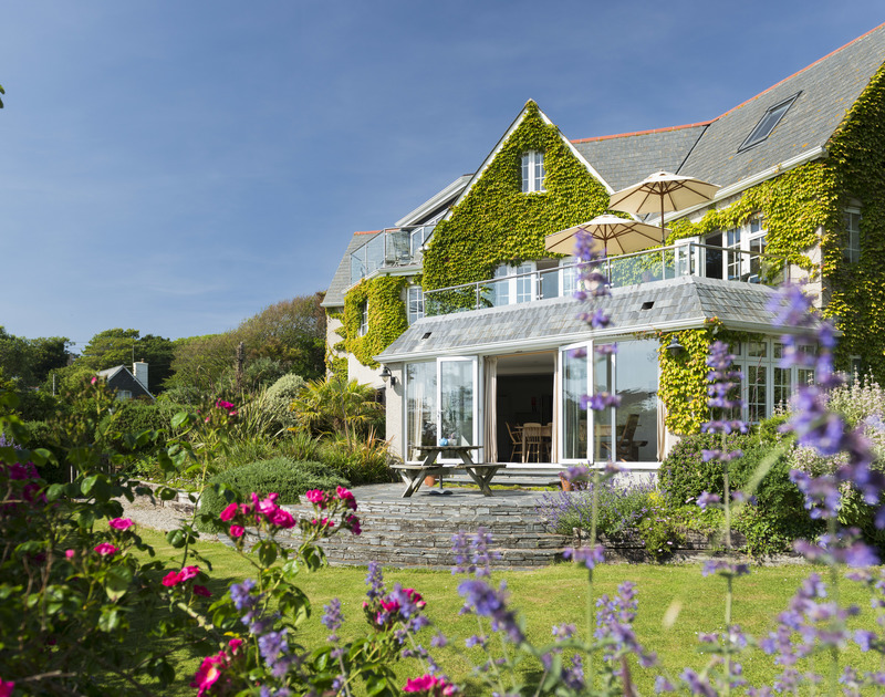 The exterior view of Bodare 1, a holiday apartment at Daymer Bay, Cornwall, with pretty garden and sunny patio.