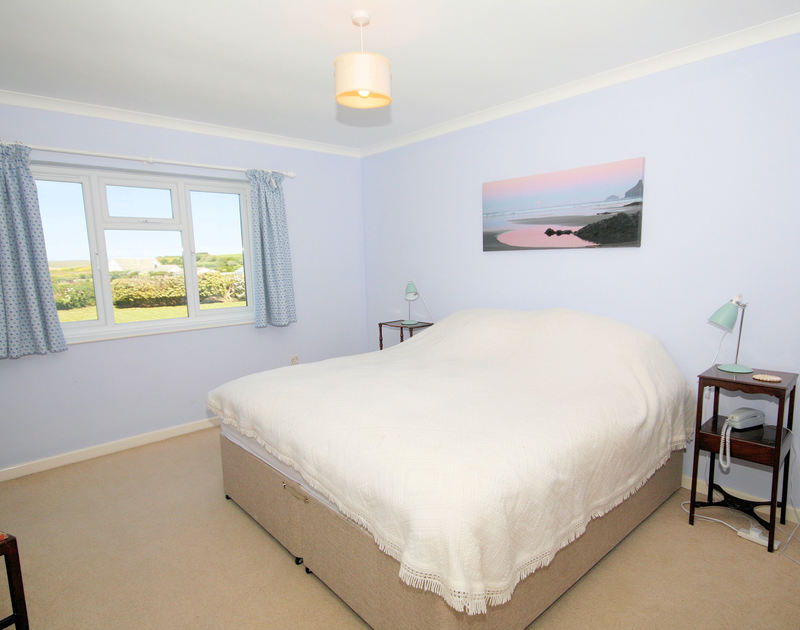 The comfortable master king size bedroom with en-suite at Trebartha, a self catering holiday house to rent in Daymer Bay, Cornwall.