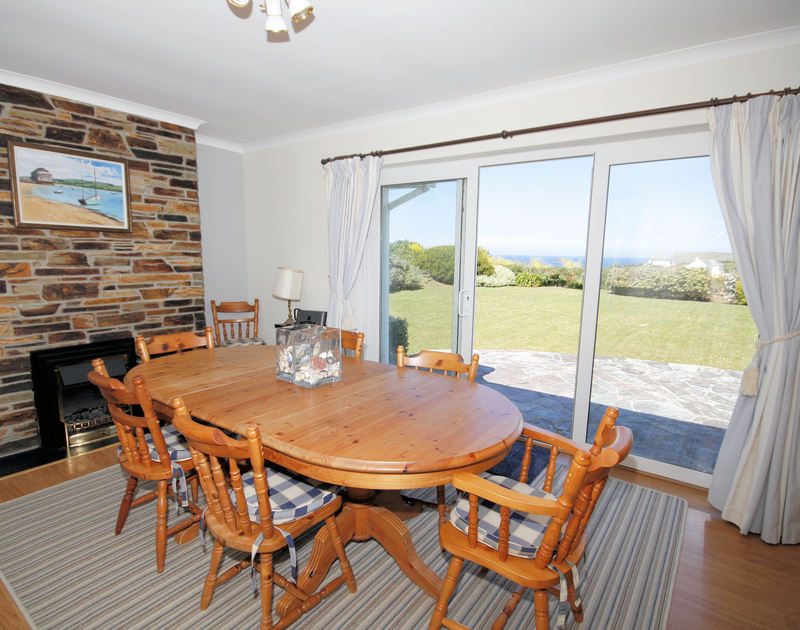 The dining room with lovely garden and sea views at Trebartha, a self catering, dog friendly holiday house in Daymer Bay, Cornwall.