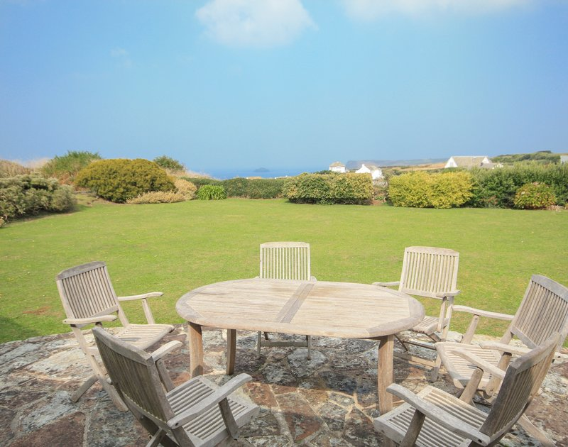 The terrace, pretty gardens and far reaching sea views from Trebartha, a self catering holiday house to rent in a wonderful setting above Daymer Bay in Cornwall.