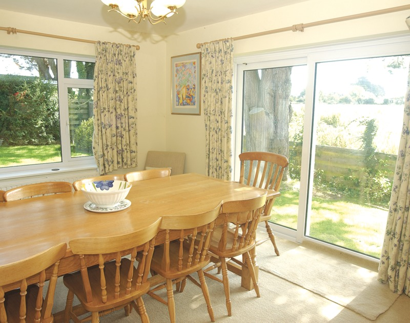 The light-filled dining room of Brookfield, a holiday house in Rock, Cornwall, with sliding doors to the garden.