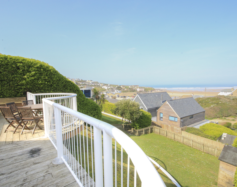 The decked balcony and seating area above the garden at Gunyah, a self catering holiday rental in Polzeath, Cornwall.