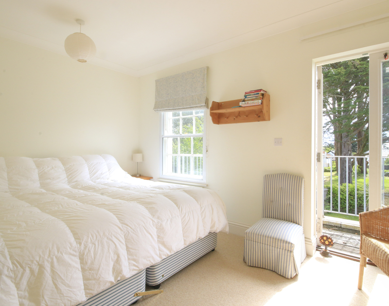 The luxurious master bedroom with french doors onto a balcony at Lowenna Manor 9,  a self catering holiday house to rent in Rock, North Cornwall.