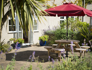 The sunny paved courtyard of Bodare 3, a holiday apartment at Daymer Bay, with picnic table and sunshade.