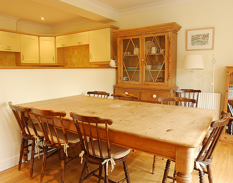 The open-plan dining room of Bodare 3, a holiday apartment to rent at Daymer Bay, Cornwall, with large farmhouse table.