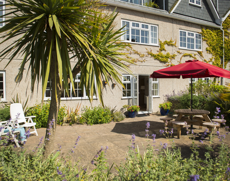 Pretty garden borders surround the courtyard of Bodare 3, a holiday apartment at Daymer Bay, Cornwall