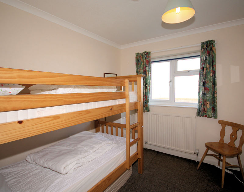 One of two bedrooms with bunk beds in Badgers Cliff, a dog friendly holiday rental in Polzeath, Cornwall.