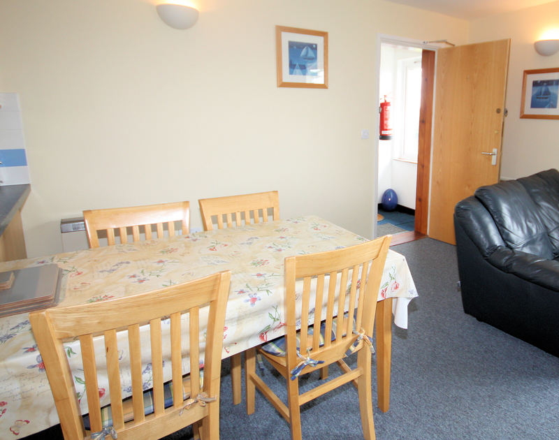 The dining table in the open plan lounge/kitchen/diner in Polzeath Court 4, a holiday rental in New Polzeath, Cornwall.