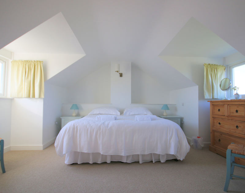 A superkingsize double bedroom at Penrhyn, a holiday rental at Daymer Bay, Cornwall, with ensuite bathroom.