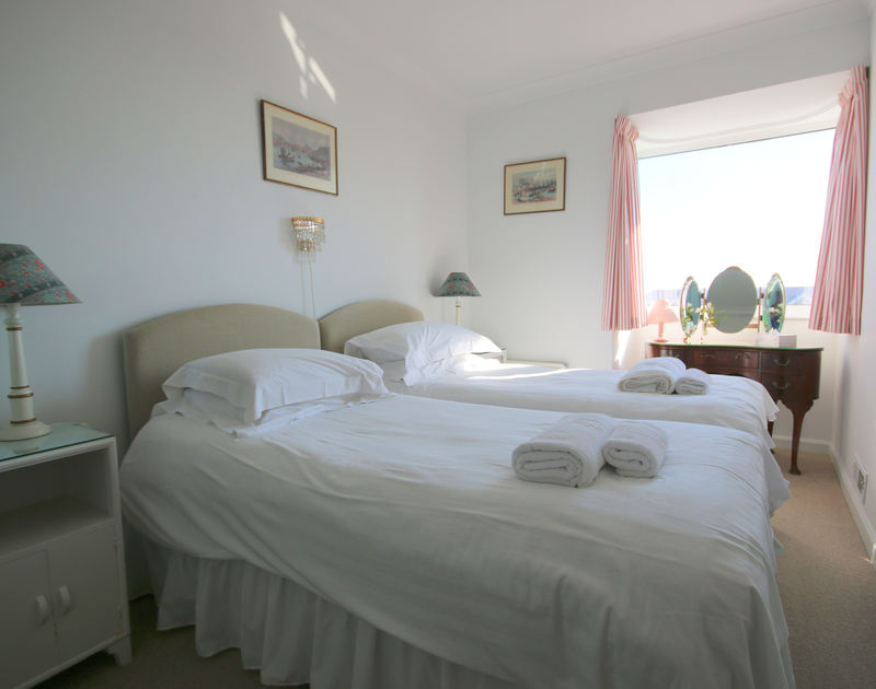 An elegantly furnished twin bedroom at Penrhyn, a holiday house at Daymer Bay, Cornwall.