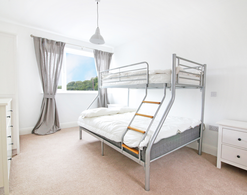 The fresh, stylish bunk room of Flat 1, The Parade, a self-catering holiday apartment in Polzeath, Cornwall