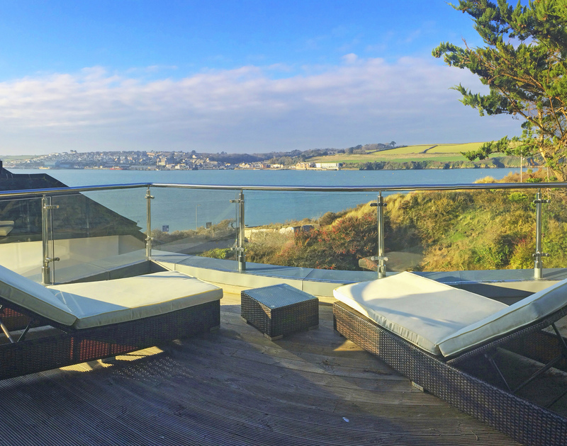 Reclining sun loungers on the balcony with far reaching Camel Estuary views over to Padstow from The Lighthouse, a luxurious holiday house to rent in Rock, Cornwall.