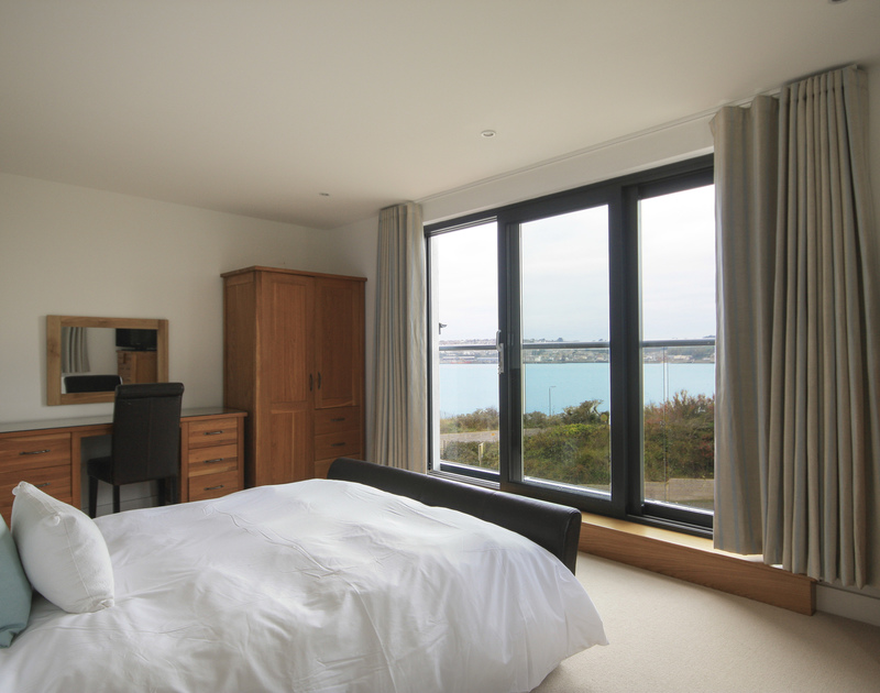 A bedroom with stunning Camel Estuary views towards Padstow in The Lighthouse, a luxury holiday rental in Rock Cornwall.