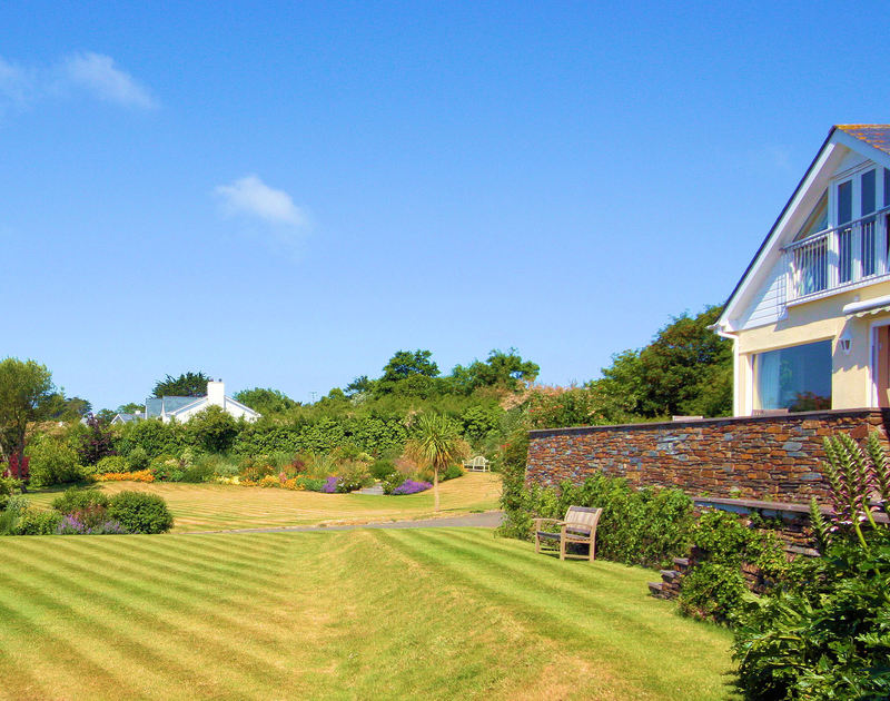 The large lawns and well-maintained garden borders of Tamarisk, a holiday house in Rock, Cornwall