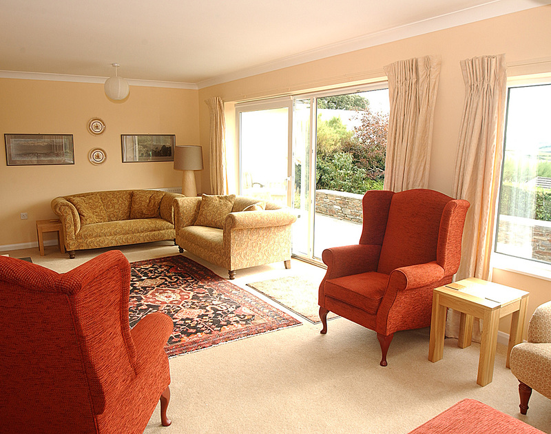 Plenty of seating in the sitting room of Tamarisk, a holiday house in Rock, Cornwall, with sliding doors to the garden.