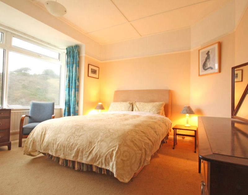 The comfy double bedroom of Seaspray, a holiday house to rent in Polzeath, Cornwall, with kingsize bed.