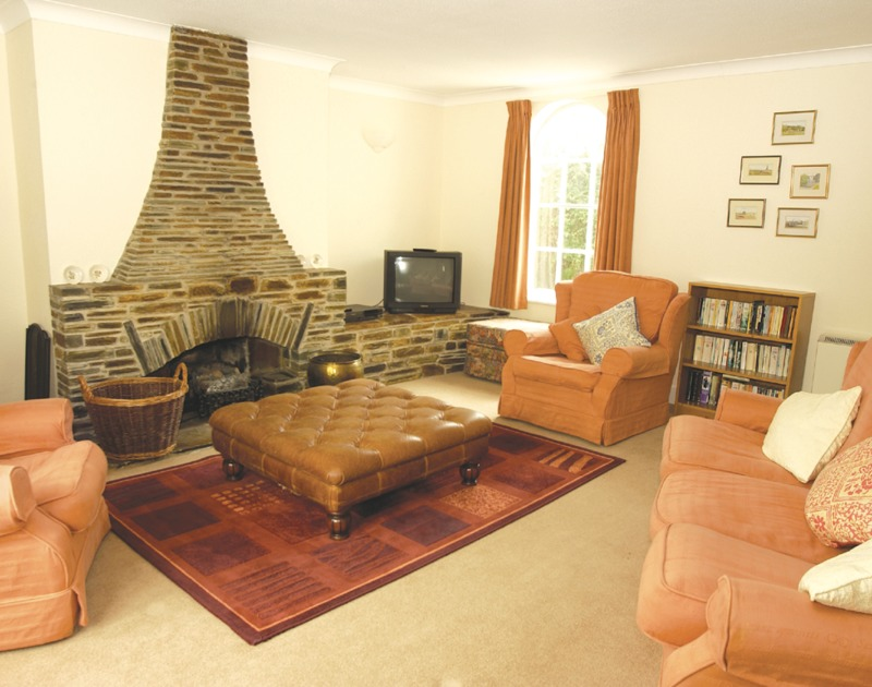 The comfy sitting room of Guelder Rose, a holiday house to rent in Rock, Cornwall, with its open fire.