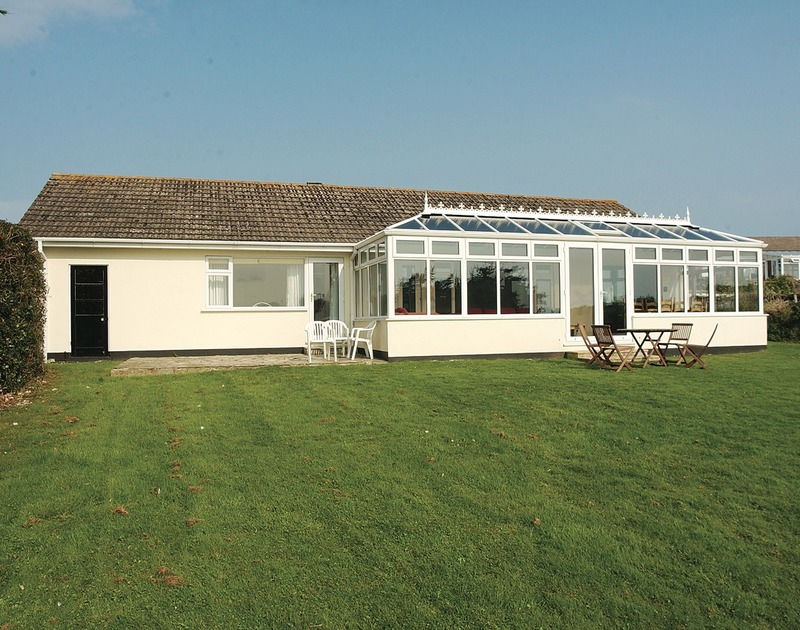 The view from the garden of the lawn and conservatory at Sandlings, a self catering holiday house to rent in popular Daymer Bay, Cornwall.
