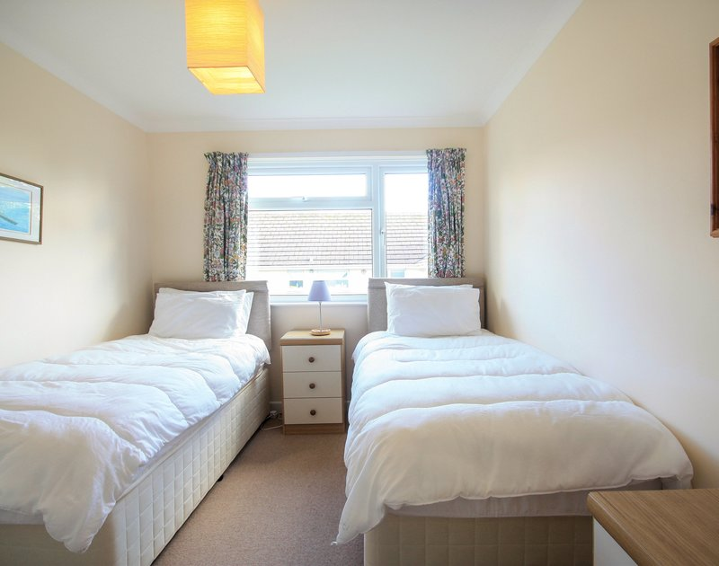 One of two comfortable twin bedrooms in Little Sailing, a holiday rental in Rock in North Cornwall.