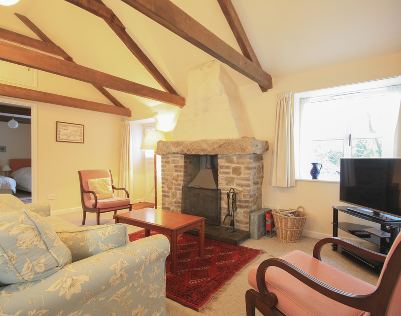 The sitting room with multi fuel stove in Mill Pond, a pet friendly, rural holiday retreat in Rock, North Cornwall.