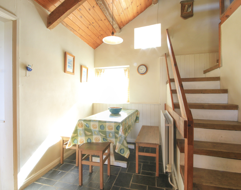 The staircase and table in the kitchen in this reverse living holiday house Mencarrek, available to rent in peaceful St MInver, Rock, Cornwall.