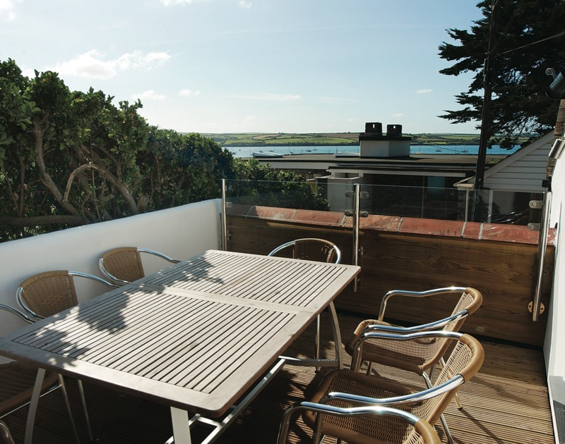The sunny sheltered decked terrace at Sea Cottage, a self catering holiday cottage to rent in Rock, Cornwall.