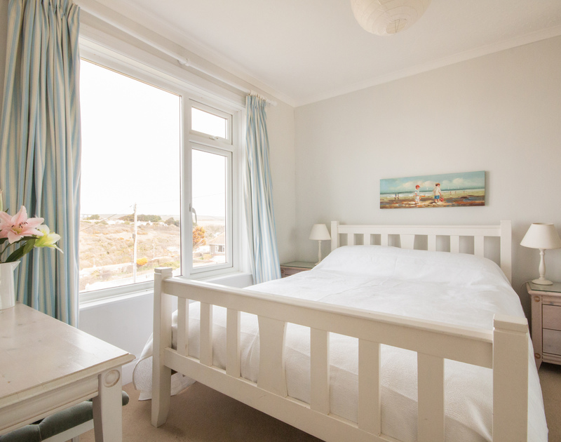 The elegantly furnished double bedroom of Treverbyn, a holiday house in Polzeath, Cornwall, with sea and beach views.