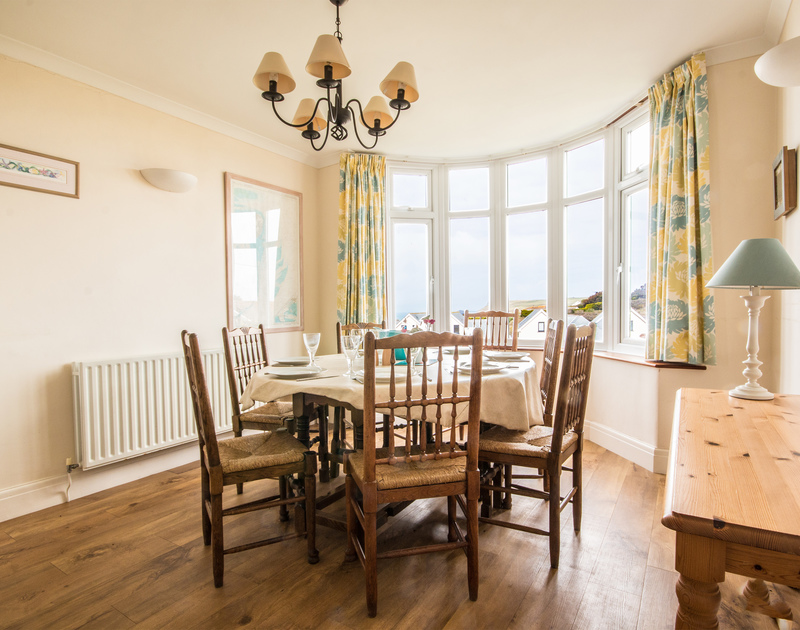 The elegant dining table area with view of the sea at Treverbyn, a holiday house in Polzeath, Cornwall