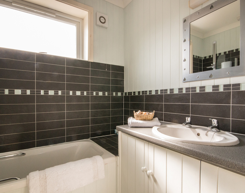 The black and white tiled modern bathroom at Treverbyn, a holiday house in Polzeath, Cornwall.