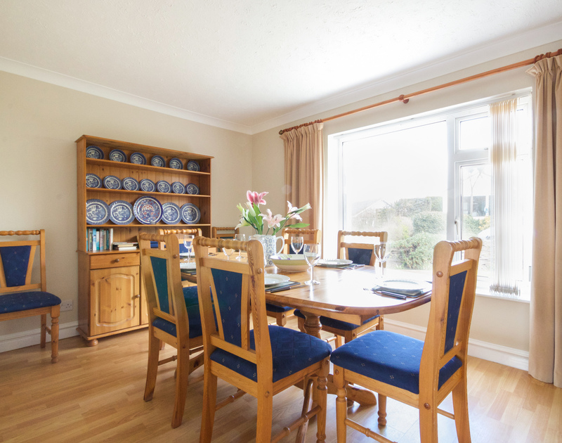 The Spacious family  dining room with large table perfect for entertaining in Sunset, a self catering holiday house in Polzeath, North Cornwall.
