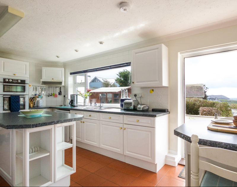 The kitchen with external glass doors out on to the terrace with stunning sea views from Sunset, a holiday house to rent in Polzeath, Cornwall.