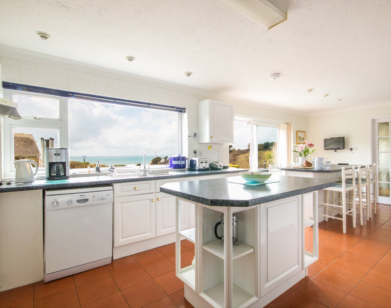 The Kitchen area and breakfast bar with superb sea views and access to patio and garden from Sunset, a self catering holiday house in Polzeath, Cornwall.