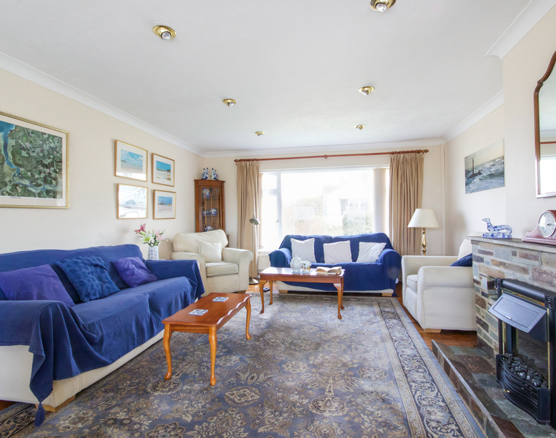 The comfortable bright sitting room with two sofas, two arm chairs  and superb sea views in Sunset, a dog friendly,holiday house to rent in Polzeath, North Cornwall.