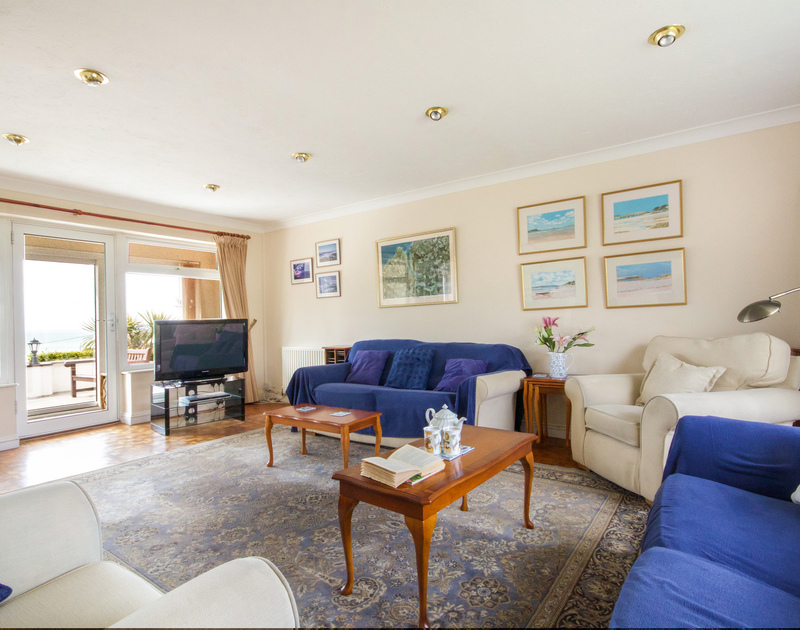 The comfortable sitting room with ample seating, television,and  wonderful views through glass doors out to sea in Sunset, a self catering holiday house to rent in Polzeath, Cornwall.