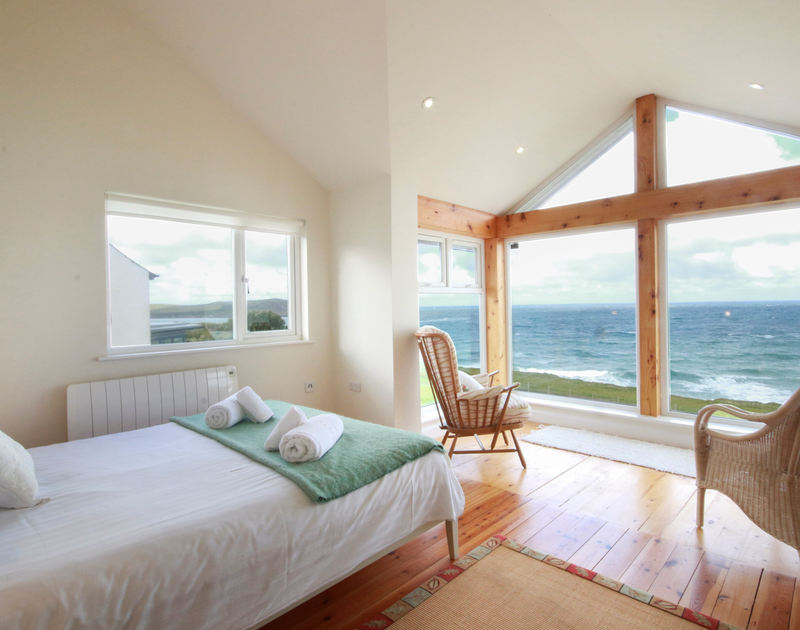 A bedroom with breath taking sea views all around at Treleven Cottage, a luxury holiday rental in Polzeath, North Cornwall.