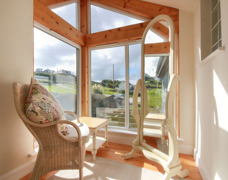 The light-filled landing with seating at Treleven Cottage, a pet friendly, luxury holiday house in Polzeath, North Cornwall.