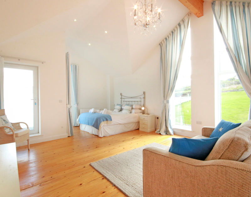 The magnificent, master bedroom in Treleven Cottage, a luxury coastal holiday retreat to rent in a fantastic setting on the cliffs above Polzeath in North Cornwall.