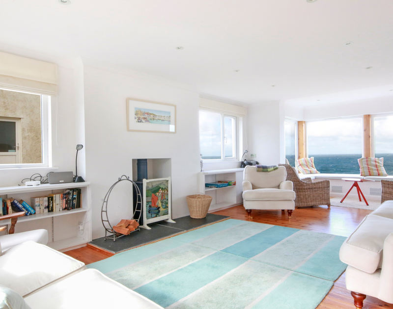 The comfortable and stylish sitting room with stunning sea views at Treleven Cottage, a luxury holiday rental in Polzeath, North Cornwall.